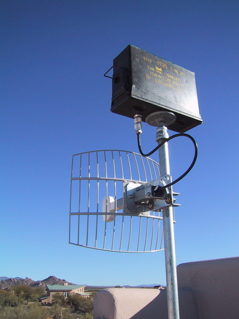 9/2002: A Wi-Fi bridge with parabolic mesh antenna. The ammo box enclosed a D-Link access point and power-over-ethernet splitter. I bridged a link just under a mile long with two units like this.