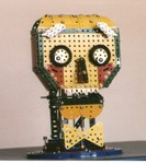 4/97: This is The Head of R&D (RAD) a robot puppet creature I built with Meccano parts for a friend's stage show. The eyes rolled, the mouth moved up and down, and the eyebrows tilted up and down, which gave him an amazing range of facial expression. I worked him through linkages from under a card table, and watched stage happenings on a wirless TV link under the table!